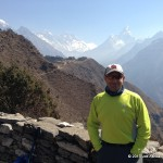 Joe Ashkar posing in front of a panoramic view of Ama Dablam & Everest.